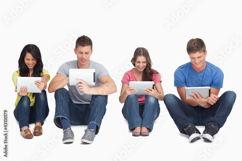 Four friends sitting on the ground all with tablets