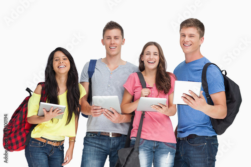A group of students with tablets and backpacks smiling and looki