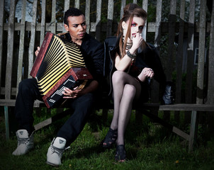 Couple young people on bench. Accordion. Countryside. Serenade