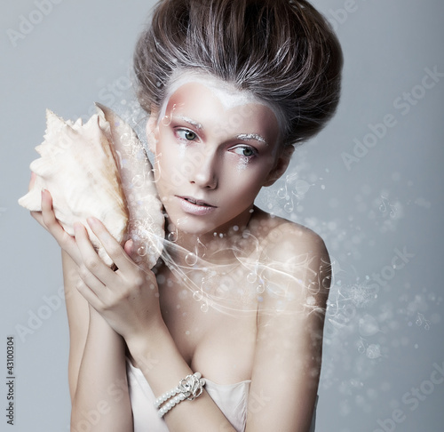 Beautiful girl with seashell in her hands. Flowing music