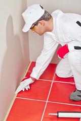 worker lays silicone sealant corner wall floor