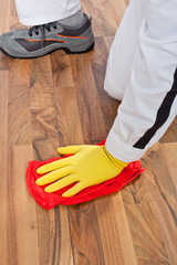 worker cleans with towel wooden floor before tilling