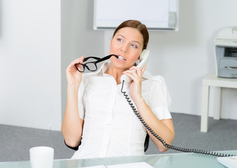 nachdenkliche sekretärin am telefon
