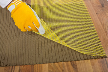 worker puts the reinforced  fiber mesh on an old wooden floor