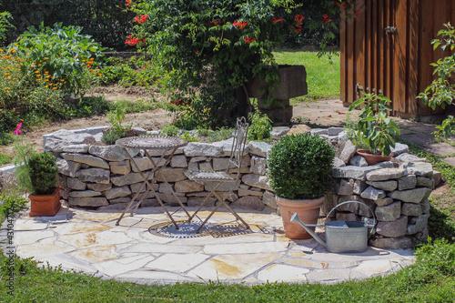 Sitzplatz im Garten mit Kräuterbeet