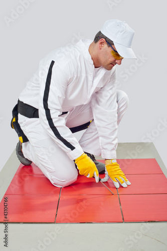 Worker with Sharp tool clean spaces between tiles remove tile ad
