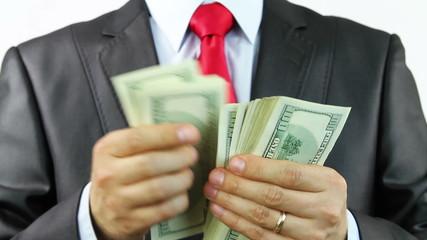 Businessman counts money in hands. Studio shot.
