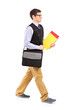 Full length portrait of a student walking with notebooks in his