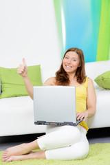 motivierte studentin sitzt mit laptop auf dem boden