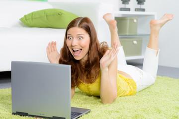 junge frau vorm laptop kreischt vor freude