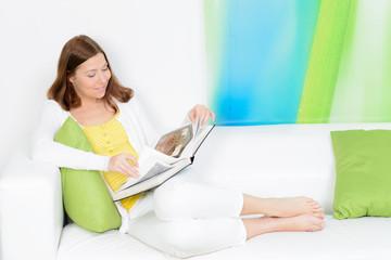 junge studentin liest auf dem sofa ein buch