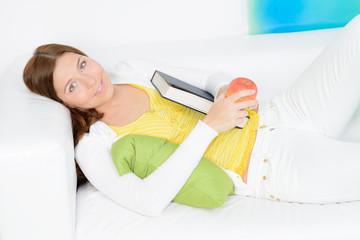 relaxte junge frau liegt mit buch auf dem sofa
