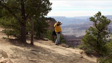 A tourist is photographing the Grand Canyon (Arizona, USA)