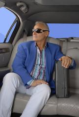 Hombre de negocios en un auto,limosina.Sujetando un maletín.