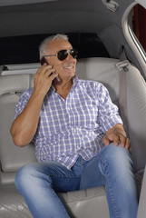 Señor casual al teléfono en un auto,señor turista.
