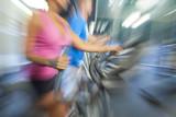 Motion Blur Zoom Man & Woman Using Gym Equipment
