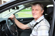 Happy mature driver with car key sitting in own car