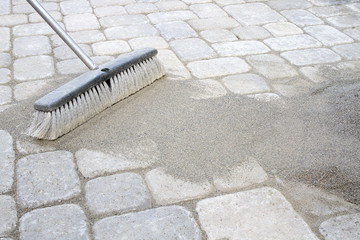 Broom Sweeping Sand into Pavers