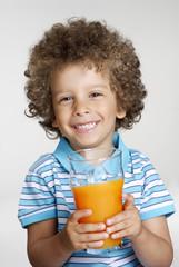 Niño sujetando un vaso de jugo de naranja,bebiendo jugo.