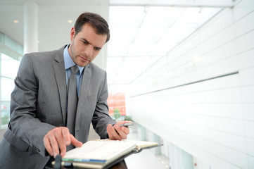 Businessman standing in hallway to check agenda
