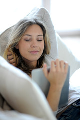 Young modern girl laying in sofa with electronic tablet