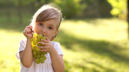 Girl eagerly eating grapes outdoors