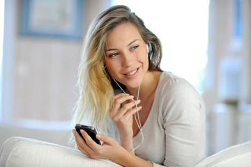 Beautiful young woman using handsfree device on mobile phone