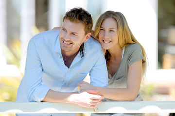 Smiling couple leaning on fence in front of house