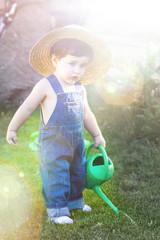 little baby gardener concentrate in his work under sunburst