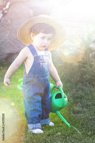 little baby gardener concentrate in his work under sunburst