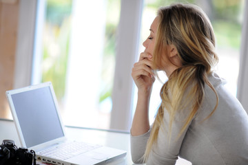 Woman sitting in front of laptop with thoughtful look