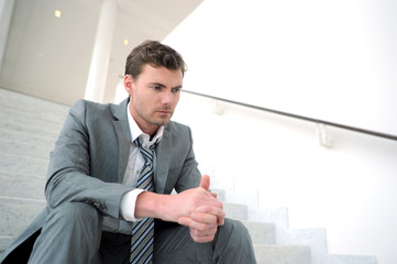 Portrait of depressed businessman sitting in stairs