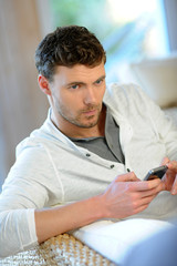 Young man sending short message with smartphone