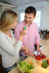Woman having her boyfriend tasting salad sauce