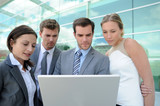 Team of business people working outside on laptop