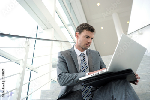 Serious businessman sitting in stairs with laptop