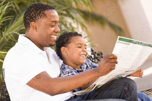 Mixed Race Father and Son Reading Park Brochure Outside