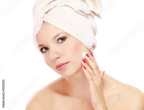 Young beautiful woman applying cream on her face © lenets_tan