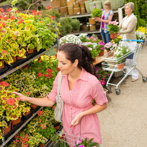 Woman choose potted flower in garden center