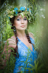 Beautiful young woman with a wreath of flowers