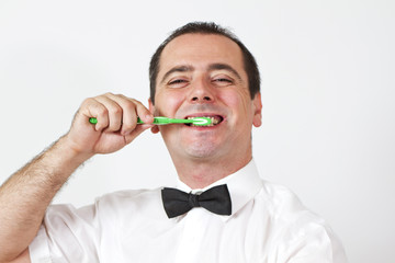 Guy with bow tie is brushing teeth