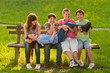 Five teenage boys and girls having fun in the park