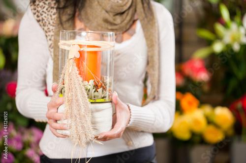 Floristin in Blumenladen mit Gesteck und Kerze