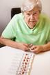 Seniorin rationiert eine Vielzahl an Medikamenten in die Pillenb