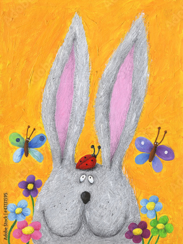 Cute rabbit in the spring with ladybug on his head
