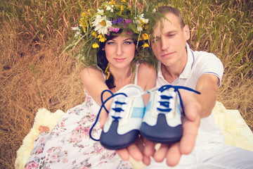 A couple in love during pregnancy in the park with young Sneaker