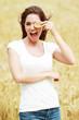 Jeune femme mangeant un gateau aux céréales dans un champ de blé