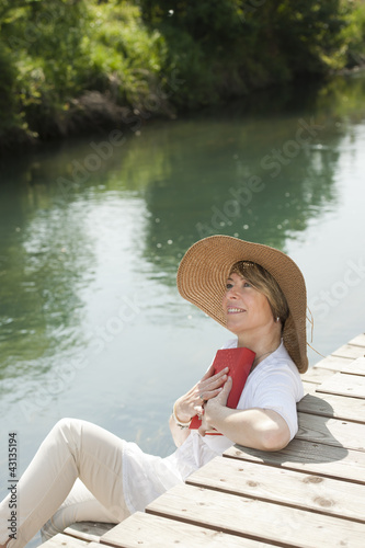 Woman reading by the river