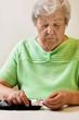 Seniorin nimmt sich Teststreifen für das Messen des Blutzuckers