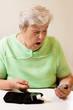 Seniorin beim Blutzucker messen ist von den Werten überrascht